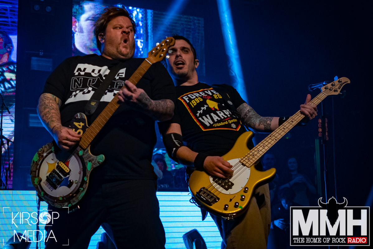 The vocalist and bassist of Bowling for Soup leaning against each other playing thier bass and guitar.