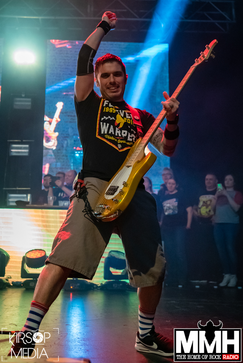 The bassist of Bowling For Soup on stage holding his bass in one had while extending his other arm above his head.