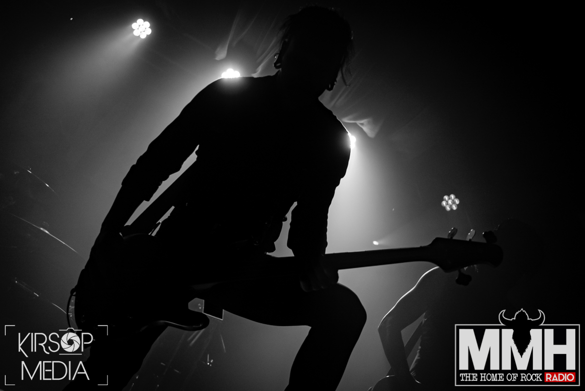 The bassist of New Years Day silhouetted on stage playing the bass.