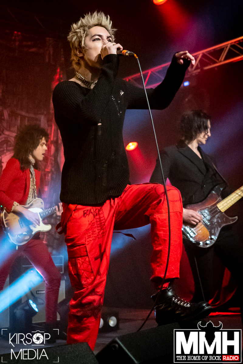 The vocalist of Palaye Royale standing with one foot on a small speaker whilst singing into a microphone.
