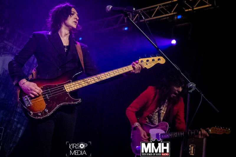 The touring bassist of Palaye Royale playing bass on stage whilst the touring guitarist is bent over playing his guitar in the background.