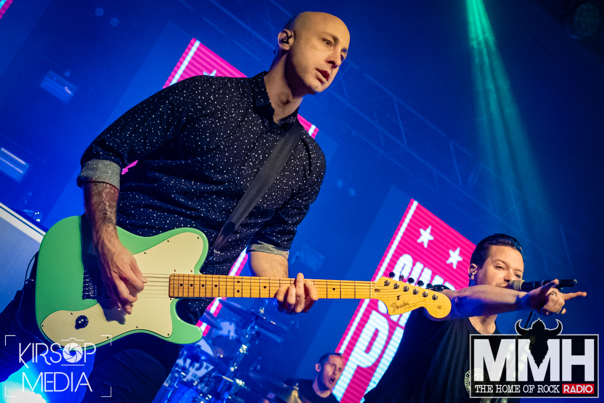 Guitarist of Simple Plan playing his guitar on stage while the bassist throws up a rock sign hand.