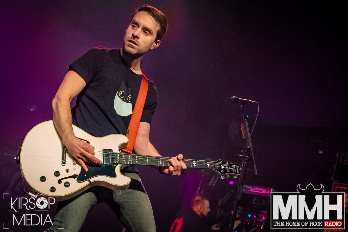 Guitarist of Simple Plan playing his guitar on stage.