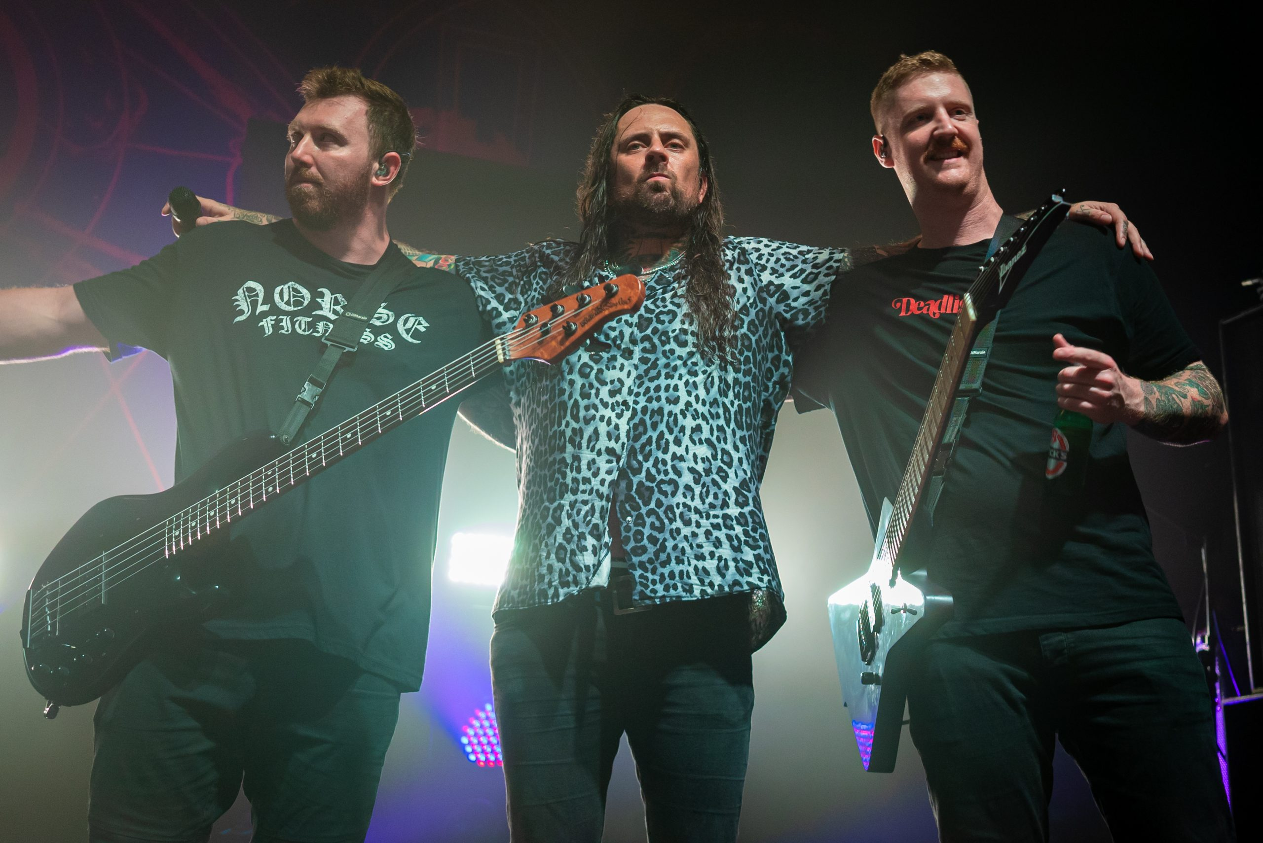 Three members of Thy Art is Murder are standing with their arms around each others shoulder whilst being back lit by purple and white lights. On the left is a bassist, in the middle is the vocalist, and on the right is the guitarist. All three members are part of an Australian death metal band.